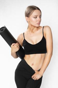Een vrouw met een geweldig figuur in sportkleding en een yogamat poseert