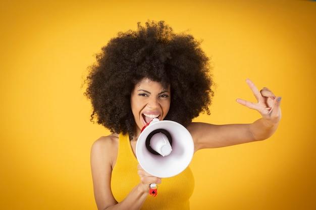 Een vrouw met een gezichtsmasker en afrohaar houdt de lgbtq gay pride-vlag op gele achtergrond