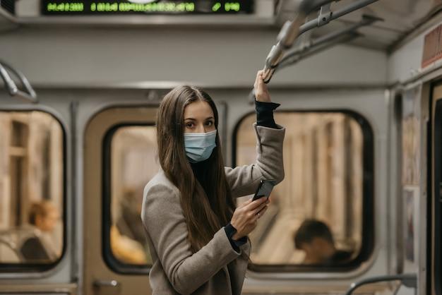 Een vrouw met een gezichtsmasker om de verspreiding van het coronavirus te voorkomen, kijkt rond in een metro. een meisje met lang haar in een chirurgisch masker op haar gezicht tegen covid-19 houdt een mobiel vast in een trein.