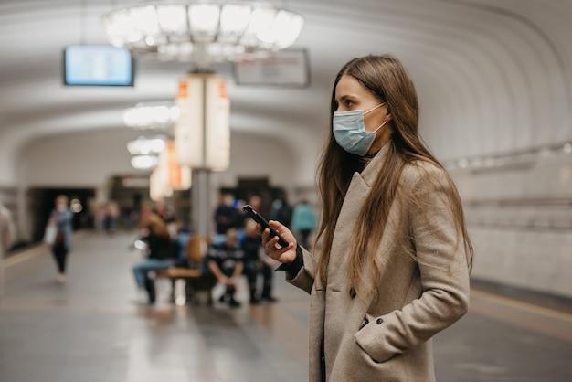 Een vrouw met een gezichtsmasker om verspreiding van het coronavirus te voorkomen, gebruikt een smartphone bij het metrostation. een meisje met een chirurgisch masker op het gezicht tegen covid-19 wacht op een trein op een metroplatform