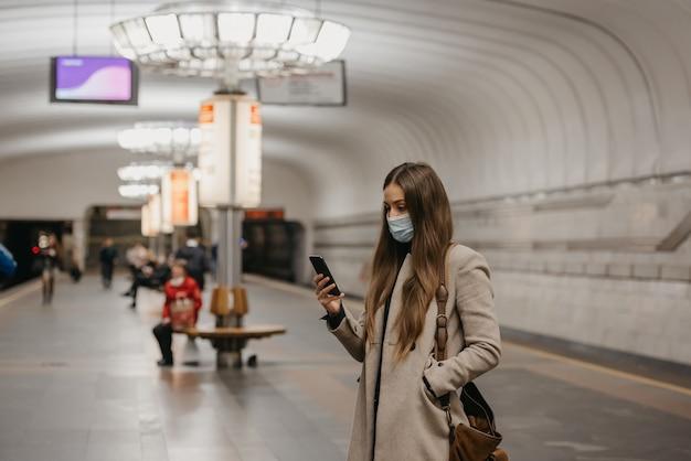 Een vrouw met een gezichtsmasker om verspreiding van het coronavirus te voorkomen, houdt een smartphone vast bij een metrostation. een meisje met een chirurgisch masker op het gezicht tegen covid-19 wacht op een trein op een metroplatform