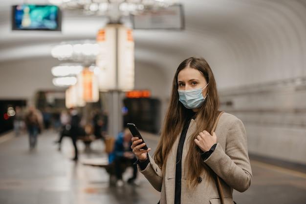 Een vrouw met een gezichtsmasker om verspreiding van het coronavirus te voorkomen, houdt haar smartphone vast bij een metrostation. een meisje met een chirurgisch gezichtsmasker tegen covid-19 wacht op een trein op een metroplatform.