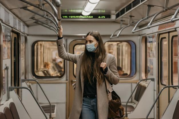 Een vrouw met een gezichtsmasker om verspreiding van het coronavirus te voorkomen, houdt zich vast aan de leuning in het midden van de metro. een mooi meisje met een chirurgisch masker tegen covid-19 staat op een metro.