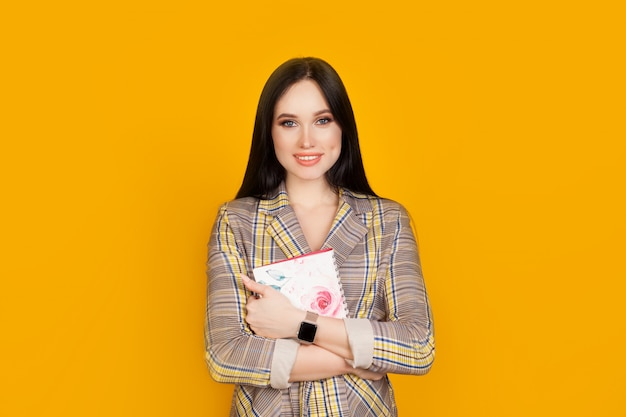 Een vrouw met een glimlach en een notebook in haar handen, in een pak op een fel gele muur, met kopie ruimte. het concept van het onderwijs, studenten of zakenvrouw.