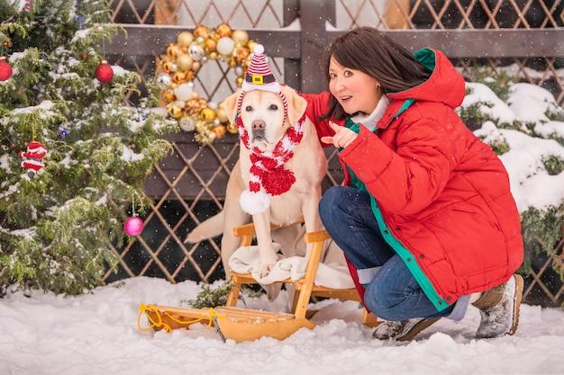 Een vrouw met een gouden labrador in een sjaal zit in de buurt van een versierde kerstboom en slee tijdens een sneeuwval in de winter op de binnenplaats van een woongebouw.