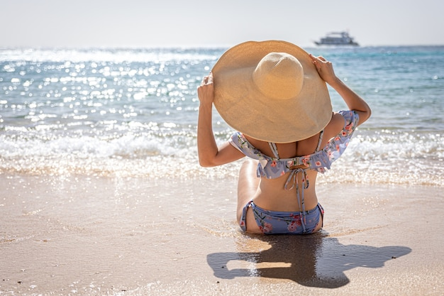 Een vrouw met een grote hoed zonnebaadt op het strand bij de kopieerruimte van de zee.