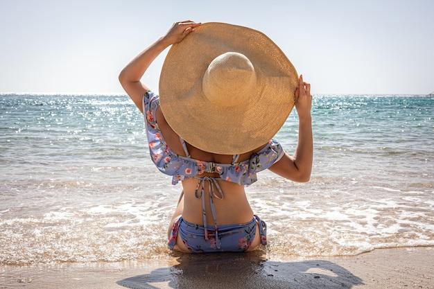 Een vrouw met een grote hoed zonnebaadt op het strand bij de zee.
