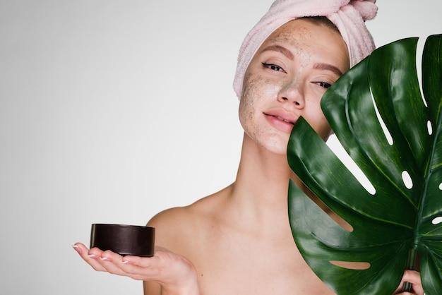 Een vrouw met een handdoek op haar hoofd na het douchen schrobde haar gezicht