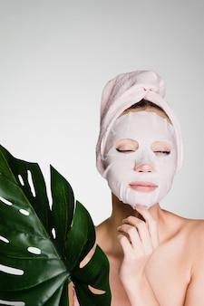 Een vrouw met een handdoek op haar hoofd na het douchen van het masker met een film op haar gezicht