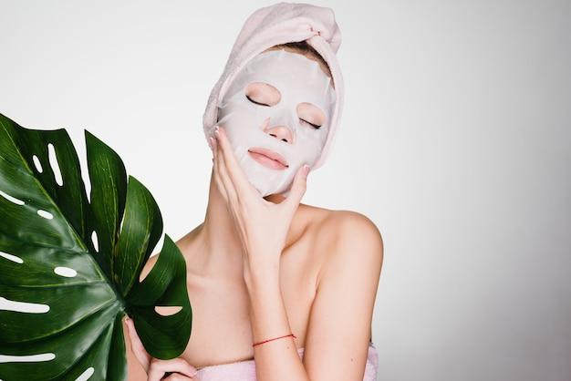 Een vrouw met een handdoek op haar hoofd na het douchen zette haar gezichtsmasker op