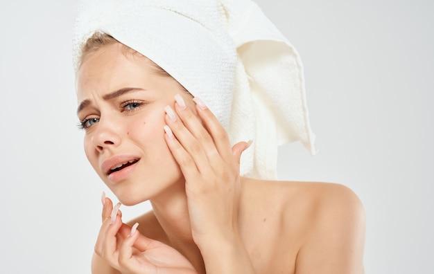 Een vrouw met een handdoek over haar hoofd raakt haar gezicht aan met haar handen op een lamp.