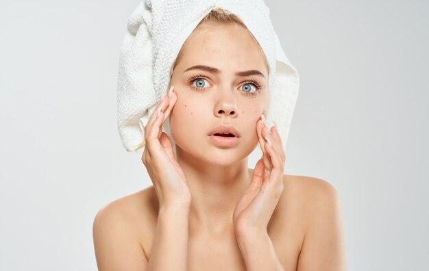 Een vrouw met een handdoek over haar hoofd raakt haar gezicht aan met haar handen op een lamp