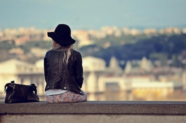 Een vrouw met een hoed en een leren jas zittend op de steen