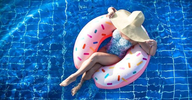 Een vrouw met een hoed ontspant zich op een opblaasbare cirkel in het zwembad.