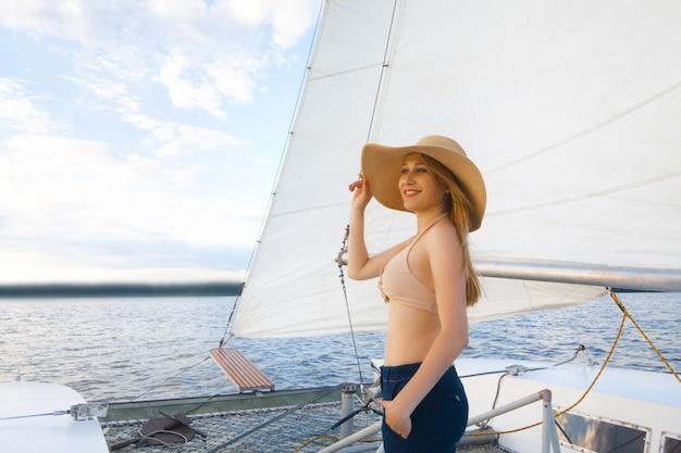 Een vrouw met een hoed op een jacht, tegen de lucht en de zee.