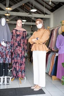 Een vrouw met een hoofddoek die een masker draagt en haar armen over elkaar slaat, staat