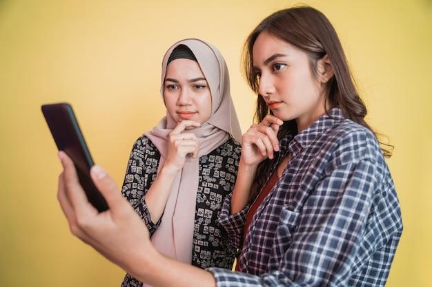 Een vrouw met een hoofddoek en een vrouw met lang haar die serieus naar het scherm van een mobiele telefoon kijken...