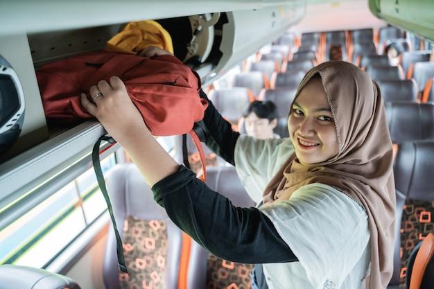Een vrouw met een hoofddoek glimlacht als ze naar de camera kijkt als ze haar tas op een plank zet terwijl ze in de bus staat