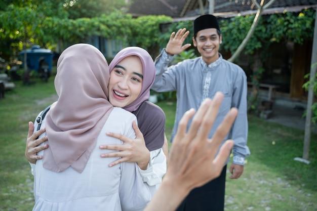 Een vrouw met een hoofddoek omhelst een vriendin