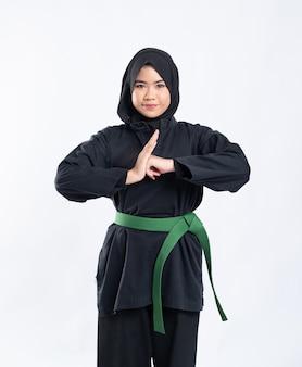 Een vrouw met een kap die een pencak silat-uniform met een groene riem draagt, voert respectvolle handgebaren uit