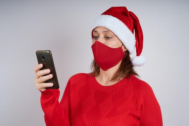 Een vrouw met een kerstmuts in een beschermend masker, in een rode trui, kijkt naar een mobiele telefoon.