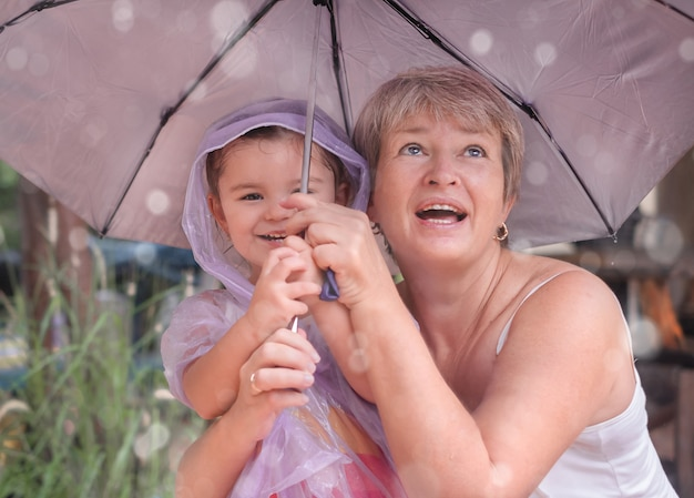 Een vrouw met een kind onder een paraplu. grootmoeder en meisje wandelen in de regen