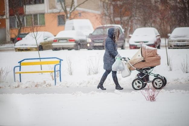 Een vrouw met een kinderwagen loopt over een besneeuwde weg. met kind wandelen in alle weersomstandigheden.