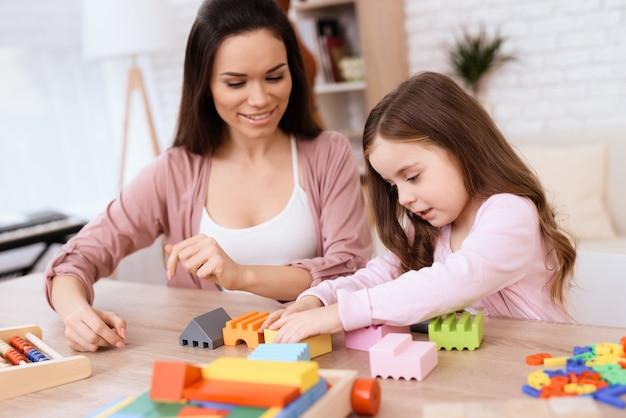 Een vrouw met een klein meisje bouwt een slot van houten kubussen.