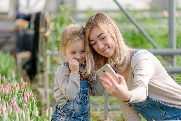 Een vrouw met een kleine dochter maakt in het voorjaar een selfie in een kas met bloemen.