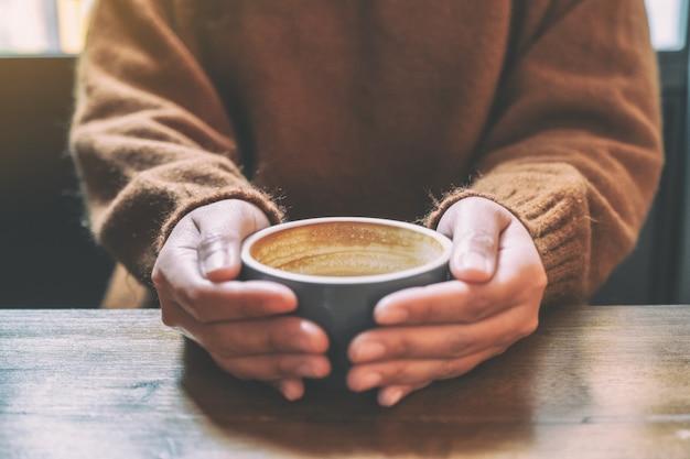 Een vrouw met een kop warme koffie op houten tafel