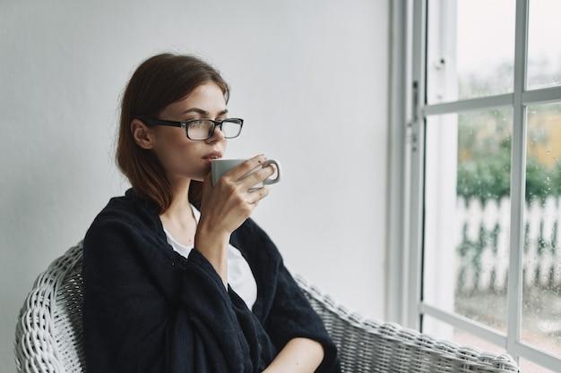 Een vrouw met een kopje koffie en een bril zit in een stoel bij het raam