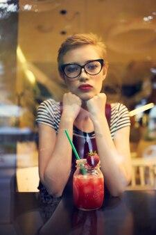 Een vrouw met een kort kapsel zit alleen in een café met een cocktail