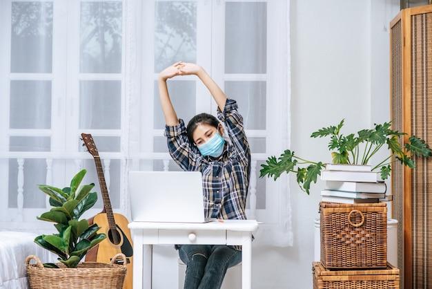 Een vrouw met een masker gebruikt een laptop op het werk en strekt haar armen uit om te ontspannen.