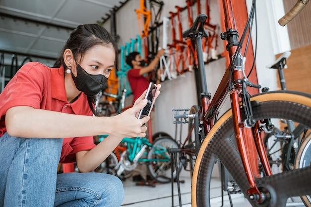 Een vrouw met een masker gebruikt een mobiele telefoon om een foto te maken van een fietsonderdeel