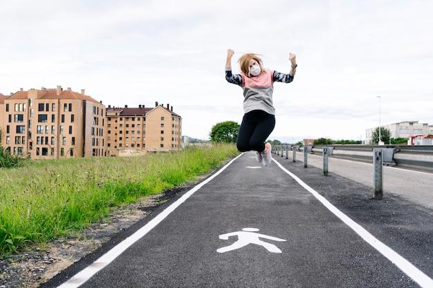Een vrouw met een masker op haar gezicht springt van vreugde naar buiten na een quarantaine