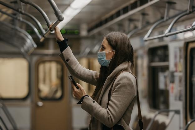 Een vrouw met een medisch gezichtsmasker om de verspreiding van het coronavirus te voorkomen, droomt in een metro. een meisje met een chirurgisch masker op haar gezicht tegen covid-19 houdt een mobiel vast in een trein.