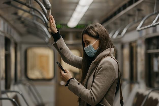 Een vrouw met een medisch gezichtsmasker om verspreiding van het coronavirus te voorkomen, gebruikt een smartphone in een metro. een meisje met een chirurgisch masker tegen covid-19 scrolt nieuws op haar mobiel in een trein.