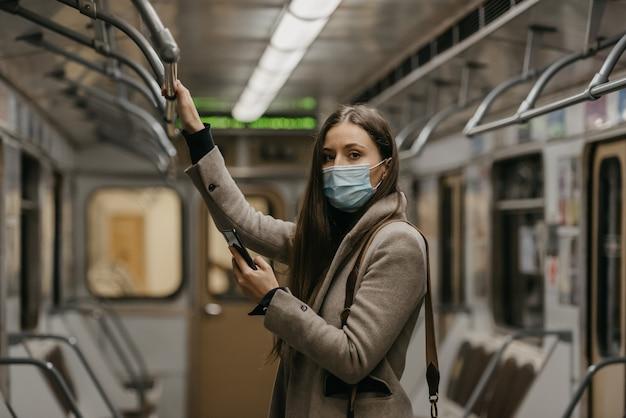 Een vrouw met een medisch gezichtsmasker om verspreiding van het coronavirus te voorkomen houdt een smartphone vast in een metro. een meisje met een chirurgisch masker tegen covid-19 scrolt nieuws op haar mobiel in een trein.