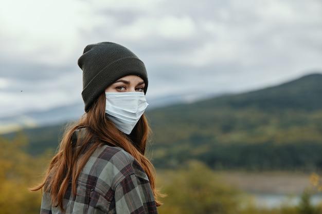 Een vrouw met een medisch masker met een hoed op haar hoofd in het herfstbos in de bergen.