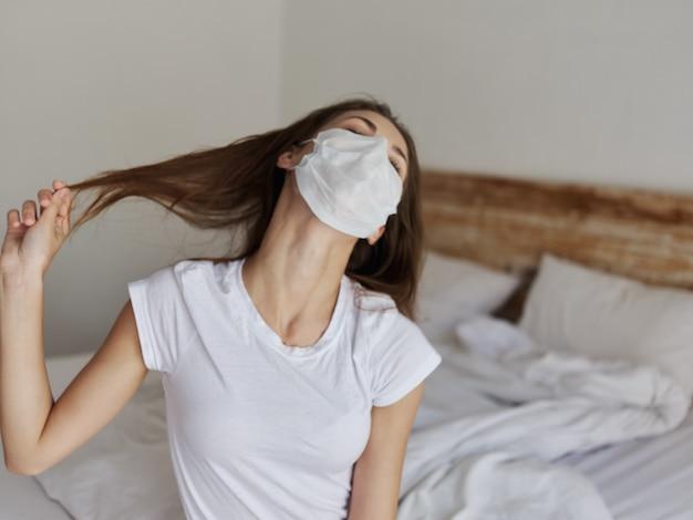 Een vrouw met een medisch masker raakt haar haar aan met haar handen en kantelt haar hoofd opzij