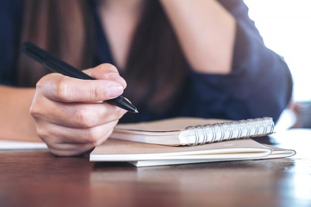 Een vrouw met een pen om op houten tafel te schrijven