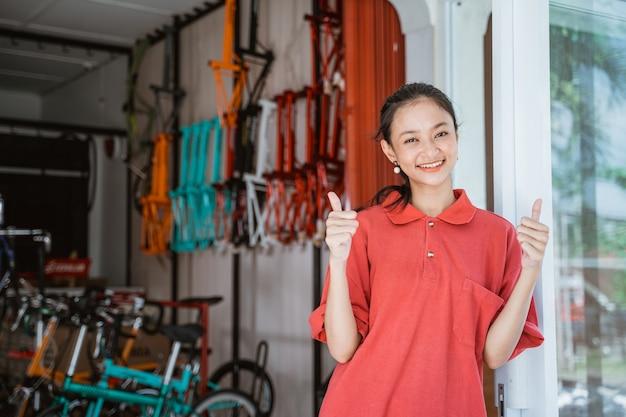 Een vrouw met een rood t-shirt met kraag en duimen omhoog die voor een fietsenstalling staat