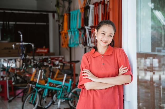 Een vrouw met een rood t-shirt met kraag en gevouwen armen staat voor een fietsenstalling