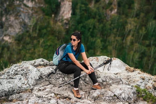 Een vrouw met een rugzak en wandelstokken in de bergen. vrouw wandelaar met wandelstokken en rugzak op een top van een berg. nordic walking op stokken. een vrouwelijke toerist. hiking. ruimte kopiëren