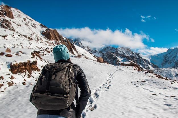Een vrouw met een rugzak maakt een klim in de bergen. blauwe lucht.