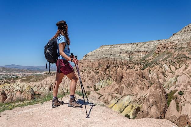 Een vrouw met een rugzak staat op een hoge berg in cappadocië en kijkt naar de veelkleurige rotsen turkije