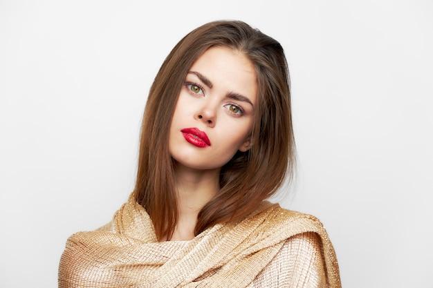 Een vrouw met een sjaal kijkt vooruit met een gekantelde hoofdmake-up