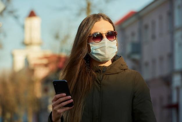 Een vrouw met een smartphone die een medisch gezichtsmasker draagt om het verspreide coronavirus op een stadsstraat bij zonsondergang te vermijden.
