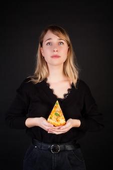 Een vrouw met een stuk pizza in haar handen, een komische emotie van gebed voor pizza.