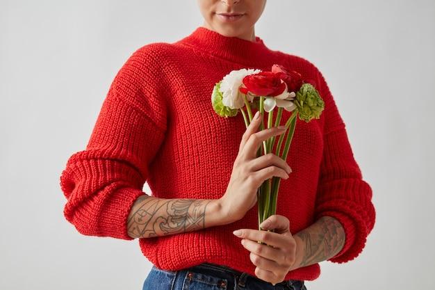 Een vrouw met een tatoeage in een rode trui houdt bloemen en een ranunculus vast. ansichtkaarten valentijnsdag